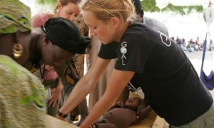 A student doing international work with community members and a baby