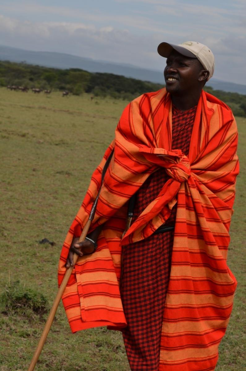 A man with a walking stick in bright cultural garb