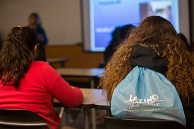 STudent in classroom with a Latino Youth Conference backpack.