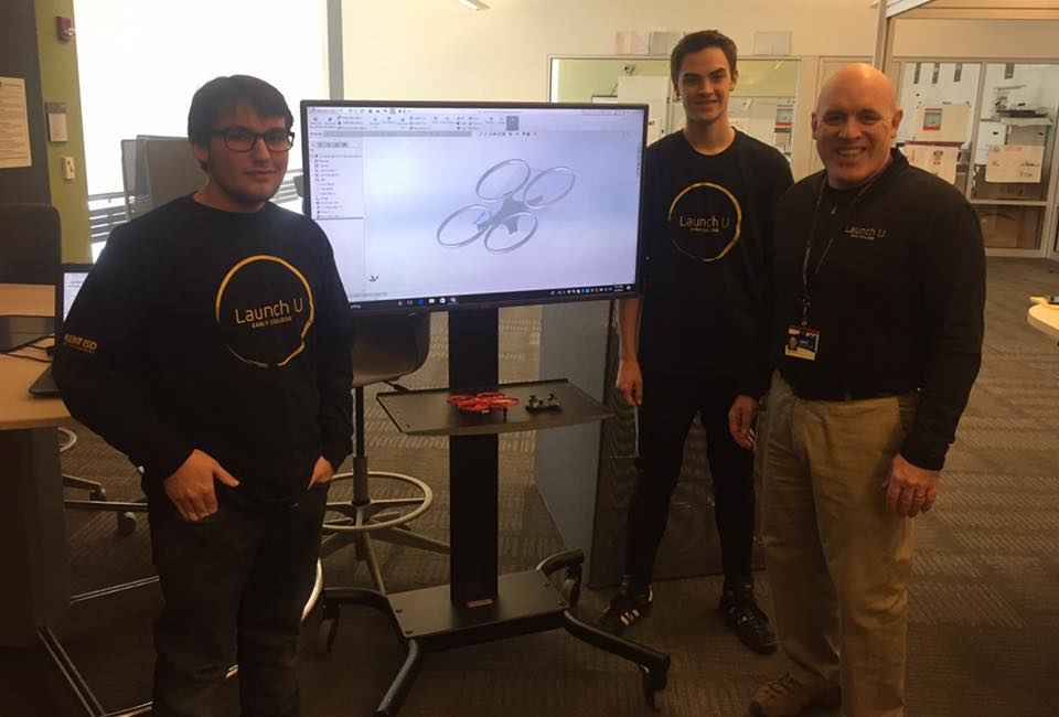 GRCC instructor Art Ward poses with Launch U students Conner Koop and Evan Oeverman standing in front of a monitor showing a photo of a drone.