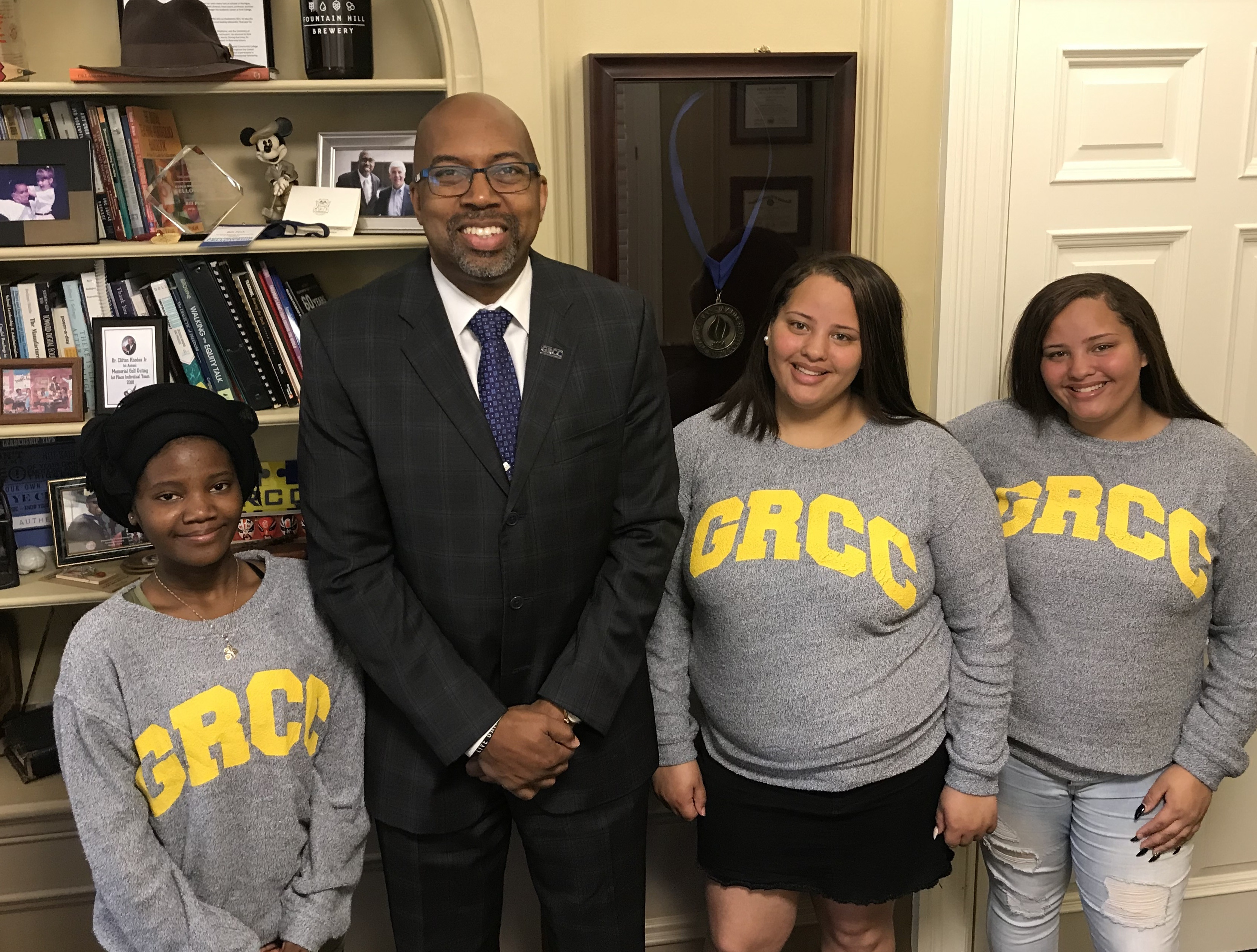 Innovation Central High School valedictorian Shamsho Abdi, Ottawa Hill High valedictorian Syena Moore and her twin sister, salutatorian Taina Moore, wearing GRCC sweaters and posing with GRCC President Bill Pink.
