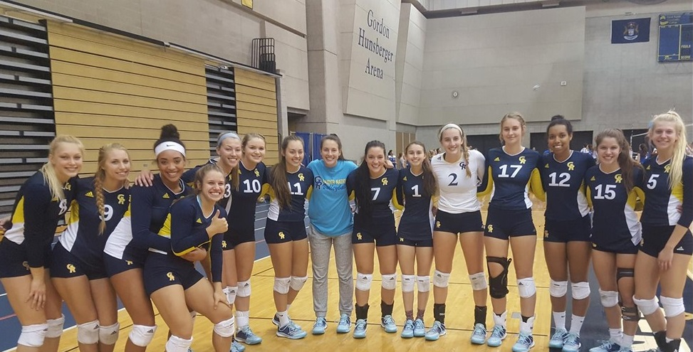 Volleyball team members stand in a row in the fieldhouse with their arms around each other.