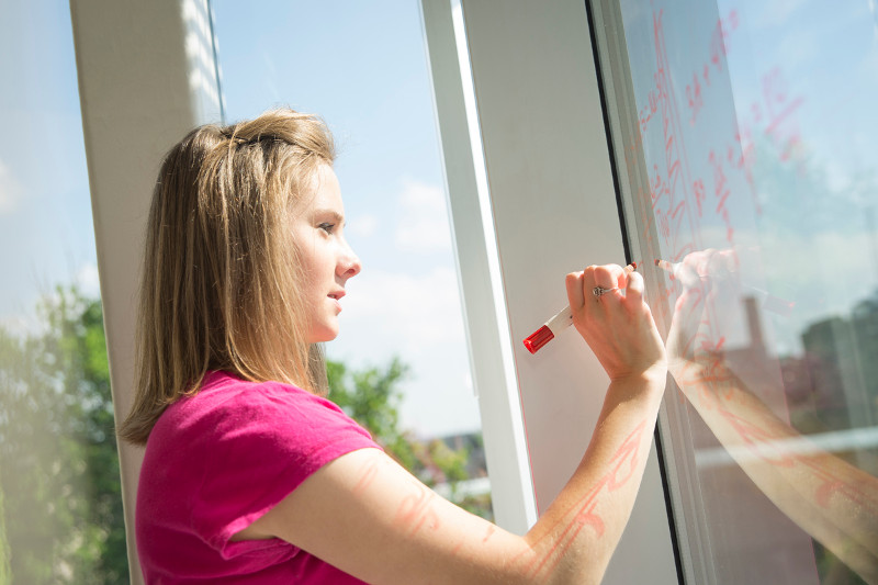 Girl in front of a window writting with a dry erase marker on a window