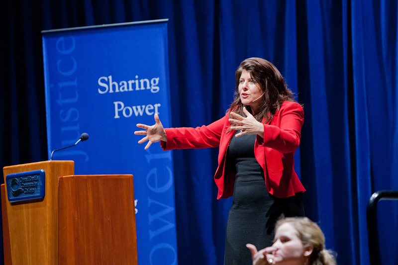 "Naomi Wolf speaking during her lecture where she stands in front of a banner that reads ""Sharing Power"""