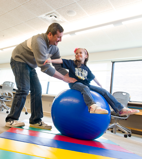 Occupational Therapy student helping young girl while she balances on a yoga ball