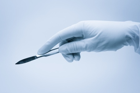 White glove holding a scalpel.