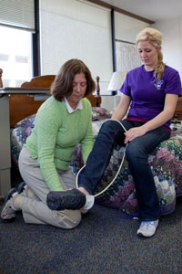 Student using sock aid tool for a patient with limited mobility with one leg.