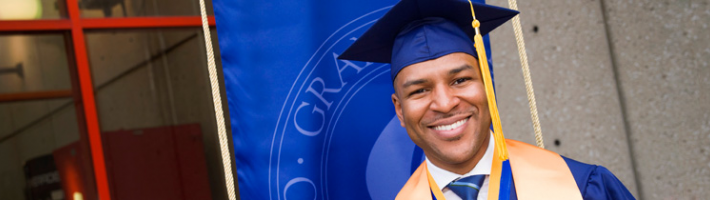 Student in graduation gown and cap smiling in front of a GRCC banner