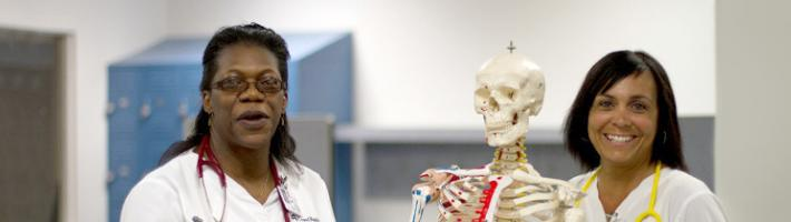 Students in the nursing department next to a plastic skeleton
