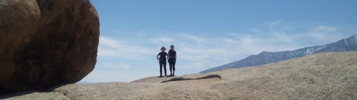 Two students standing on a rocky terrain.