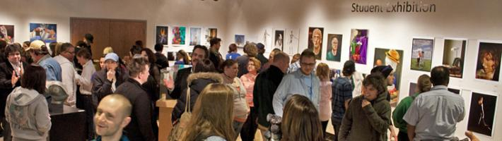 An art showing at the GRCC Collins Art Gallery with many in attendance.