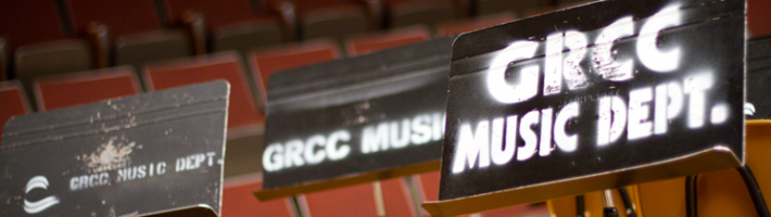 Music stands with GRCC Music Dept. spraypainted onto them in an auditorium.