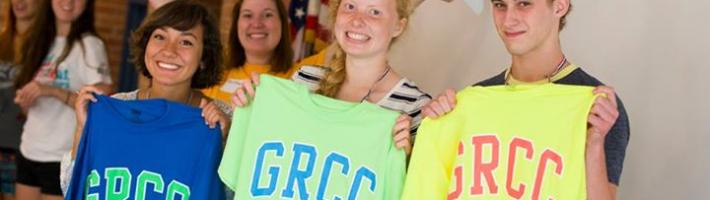 Students smiling and holding GRCC T-shirts