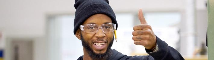 Student smiling and giving a thumbs up.