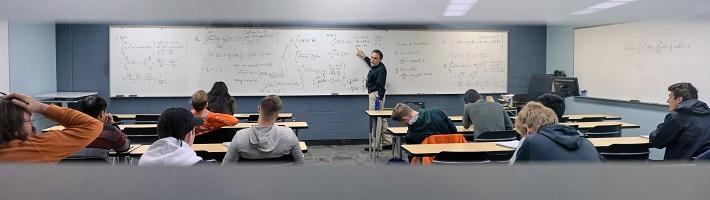 Math teacher at the whiteboard in front of his class.