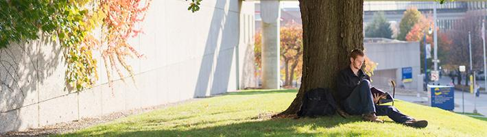 GRCC student sitting under a tree on the Main Campus.