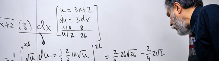 A teacher writing equations on a whiteboard.