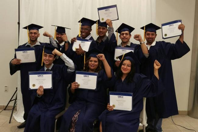 Adults education students at the 2017 graduation ceremony wearing blue caps and gowns, holding their certificates of completion.