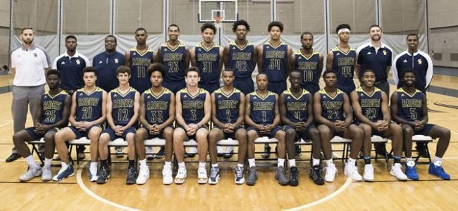 The members of the 2017-18 men's basketball team are in two rows, with the first row seated, on the fieldhouse floor.