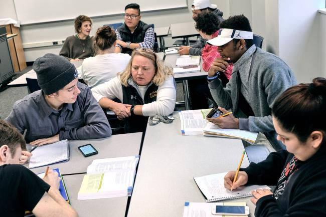 Adjunct English instructor Kaari Bloedow sits with students around a classroom table.