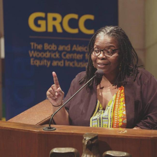 Dr. B. Afeni McNeely Cobham speaking at an event with the GRCC Woodrick Center logo over her shoulder
