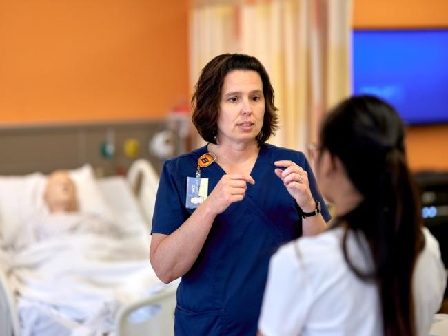 GRCC Nursing professor Brandi Miller speaking with a student in the simulation lab