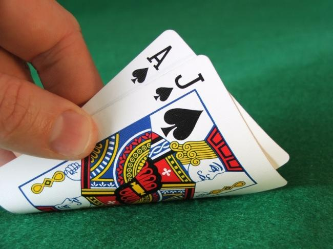 A hand is turning over two cards: the ace and jack of Spades.
