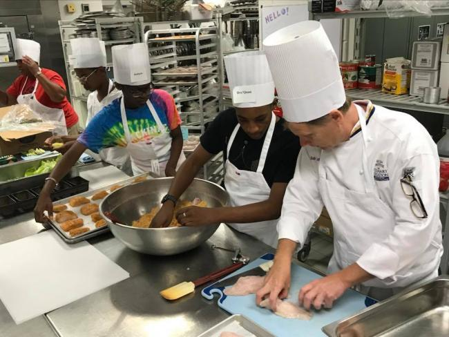 Chef Bob Schultz shows two high school students how to bread fish.