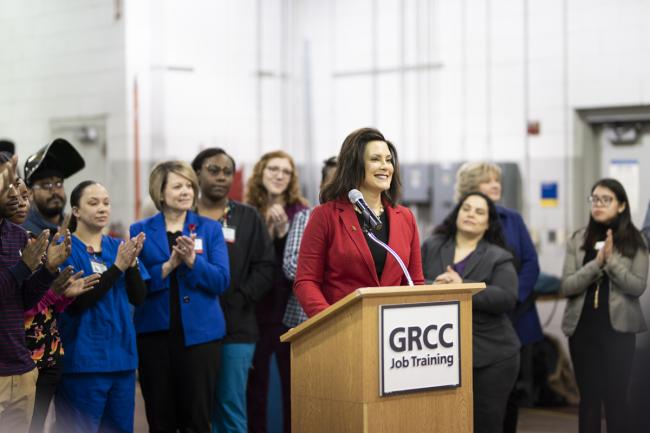 Governor Gretchen Whitmer standing at a podium in the Tassell M-TEC, surrounded by students, faculty and community partners.