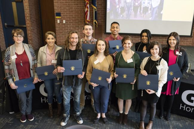 Ten students, all wearing special cords around their necks, hold up their Honors Program certificates as they stand in front of a stage in Sneden Hall.