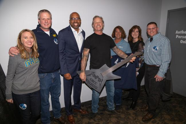 Metallica guitarist James Hetfield holds a guitar made by GRCC welding professors surrounded by GRCC President Pink and staff.                            ors