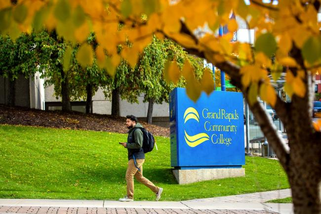 Student walking near a GRCC sign with fall foliage in the foreground.