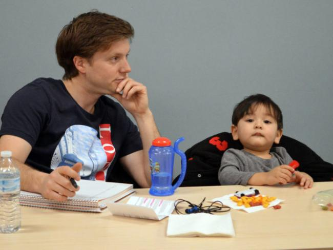 GRCC student Chad Hamilton sitting at a table attends a workshop on depression with his son, Caelan, 2, for a class he is taking