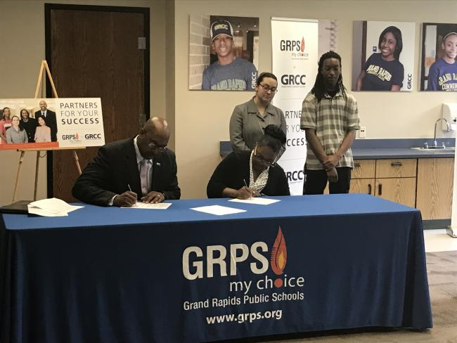 GRCC President Bill Pink and GRPS Superintendent Teresa Weatherall Neal seated at a table signing two documents that exted partnerships for concurrent enrollment and the Learning Center program. Students Najee Smith and Fatemeh Abedi are standing behind them.