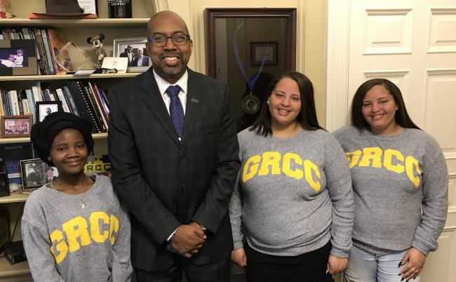 GRCC President Pill Pink posing in his office with the valedictorian from Central Innovation High and the valedictorian and salutatorian from Ottawa Hills High.