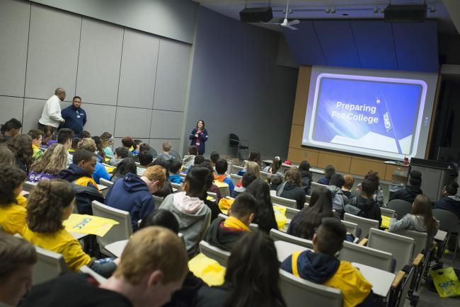 "Seated students face a video screen that says ""Preparing for College."""