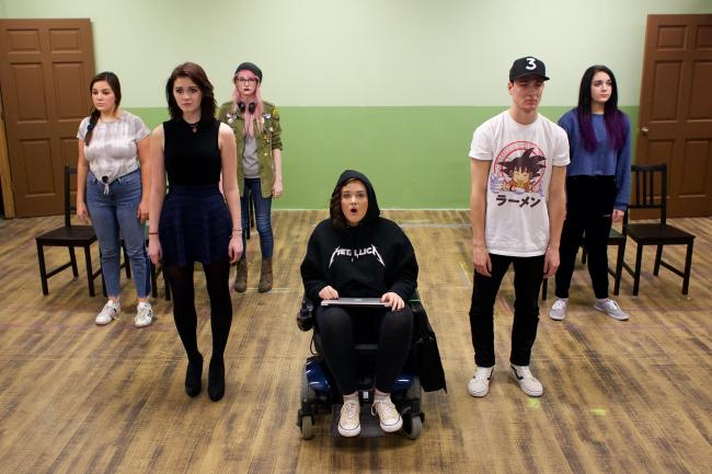 Members of the cast of 'Good Kids' stand on stage. The performer in the middle is using a wheelchair.