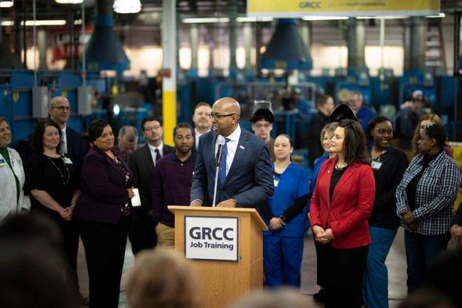 GRCC President Bill Pink speaks at a podium at the Tassell M-TEC with Governor Gretchen Whitmer standing at his side. They are surrounded by students, staff and stakeholders.