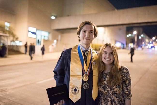 Marcus Barissi, in a graduation cap and gown, stands with a young woman on Lyon Street.