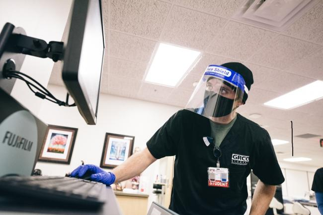 Radiology student with face coverings looking at xrays on a computer screen.