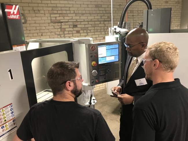 GRCC President Bill Pink with two students looking at machinery at the AMP Lab