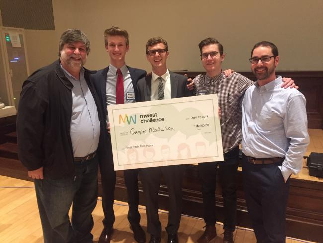 GRCC professor Felix Pereiro stands with ), Aiden Wysocki, Jake Dabkowski, Matthew Veenhoven and Jonathan Moroney, who all hold a giant check.