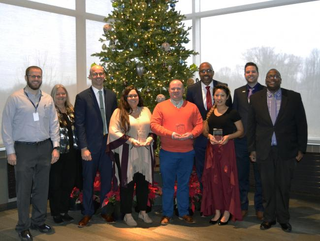 Nine people, including President Pink and Aruna Khadka, stand in front of a Christmas tree in the lobby of Frederik Meijer Gardens.
