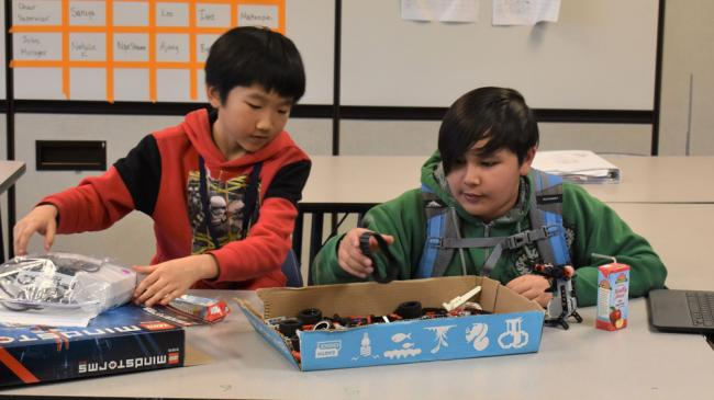 Kelloggsville Middle School students Cody Liang and Eman Marasigan look through a box of parts for their robot.