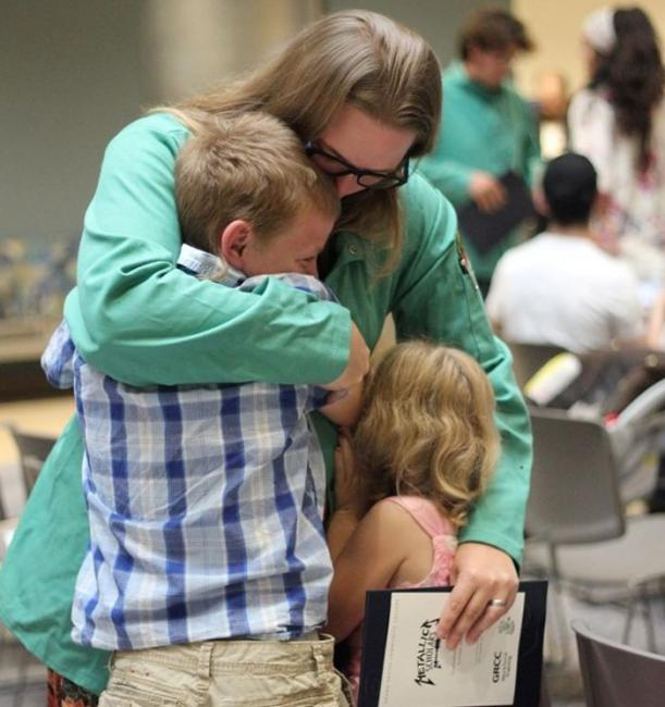 Metallica Scholar Krista Steffens hugs her two children after earning her certificate