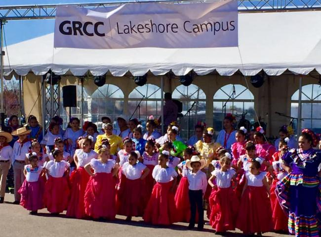 Children dancing in traditional Latino clothing in front of a stage at the LAUP Fiesta.