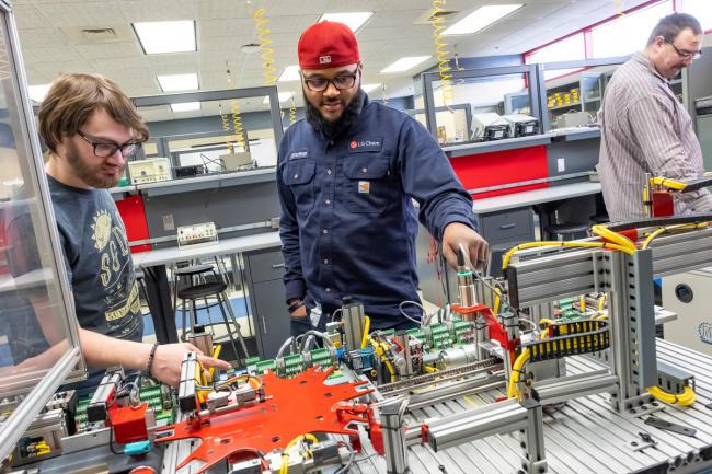 Two students work with equipment in the Mechatronics lab.