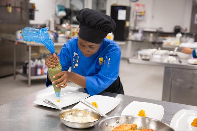 Student from Barbados in a black chef's hat and blue kitchen coat squeezing ingredients from a funnel during competition.