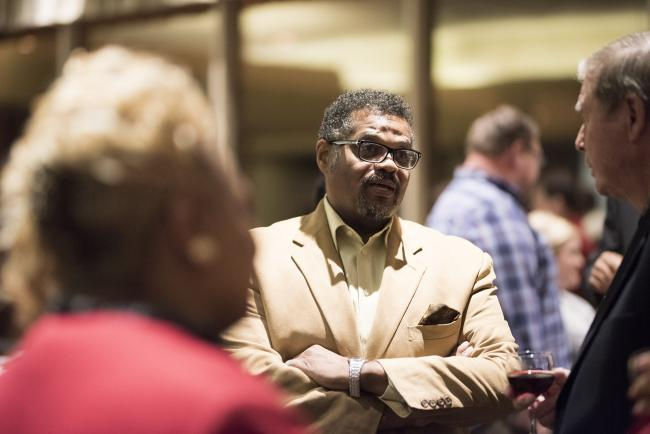 Rev. Nathaniel Moody speaking with colleagues at a reception.