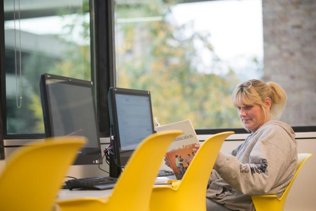 A female GRCC student sitting in a computer lab, looking at a text book.